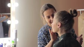 Make-up artist touchs up the face of young modal stock video