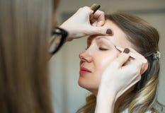 Make-up artist tweezing eyebrow. Royalty Free Stock Image
