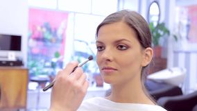 Make-up artist using brush and powder to model's makeup in studio stock footage