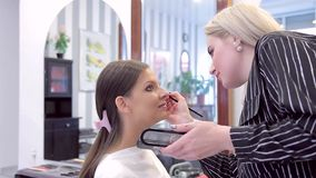 Make-up artist is using eye-shadow in models make-up stock footage