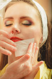 Make up artist using oil absorbing tissues sheets. Closeup of visagiste and pretty young women girl. Beauty and makeup concept royalty free stock images