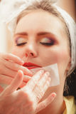 Make up artist using oil absorbing tissues sheets. Closeup of visagiste and pretty young women girl. Beauty and makeup concept Royalty Free Stock Photo