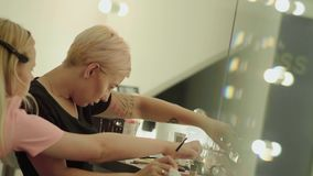 Make-up artist at work. In the beauty salon. Girl holds a brush in her hand and opens a small jar of powder stock footage