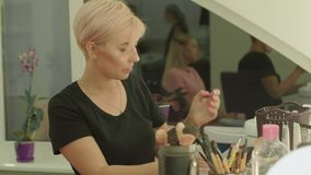 Make-up artist at work. In the beauty salon. Girl opens a small jar of powder and takes a brush stock video