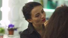 Make up artist at work. Make up artist dark form pulls out the girl`s eyebrow using tweezers. Make up artist in a dark shirt and with dark hair stock footage