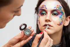 Make-up artist working with colors on model face Royalty Free Stock Image
