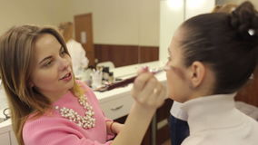 Make-up artist working in a crowded beauty salon. stock video footage