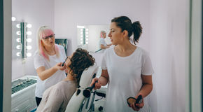 Make-up artist working with a female customer Stock Photos