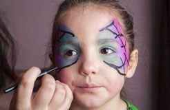 Make-up artist working with a little girl before halloween party Stock Photos