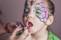Make-up artist working with a little girl before halloween party Stock Image
