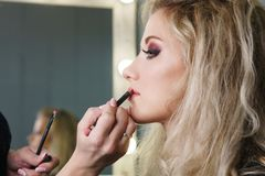 Make up artist working in make up studio, applying makeup stock photography
