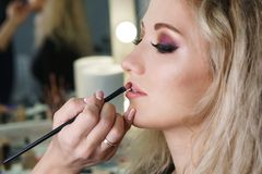 Make up artist working in make up studio, applying makeup royalty free stock image