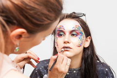 Make-up artist working on model lips before photo shooting Stock Image