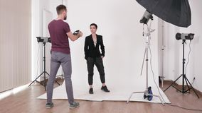 Make up artist working on a photo set. With a professional model and photographer stock video