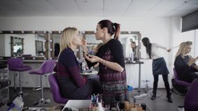 Make-up artist is working preparing model for future shooting. Brunette female master is applying cosmetics on client`s stock video footage