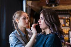Make-up artist working with woman client Stock Images