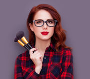 Make-up artist. Young make-up artist with brushes on grey background Royalty Free Stock Photo