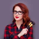 Make-up artist. Young make-up artist with brushes on grey background Stock Images