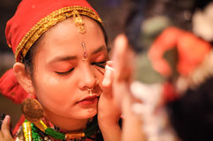 Make-up in Assam. Guwahati, Assam - circa April 2012: Young native girl with red headcloth and earrings gets her eye lined by eye pencil at Bihu festival in Stock Image