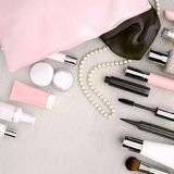 Make up bag with cosmetics located on the white wooden backgroun Stock Photography
