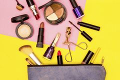 Make up bag with cosmetics on yellow and pink background. stock photos