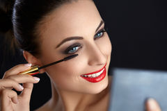 Make-up. Beautiful Woman Doing Makeup. Mascara Brush. Red Lips Royalty Free Stock Photos