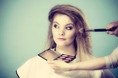 Makeup artist applying with brush rouge on female check Royalty Free Stock Photo