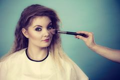 Makeup artist applying with brush rouge on female check royalty free stock image