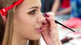 Make-up in a beauty salon, makeup artist paints the eyes of a young girl, a brush for applying shadow in his hand