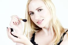 Make-up: Blond girl 13. Young blond girl doing make-up royalty free stock photography