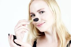 Make-up: Blond girl 14. Young blond girl doing make-up royalty free stock photos