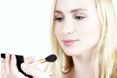 Make-up: Blond girl 16. Young blond girl doing make-up stock image