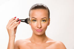 Make up. Brown sleek hair beautiful woman with fan brush close to face looking at the camera. Royalty Free Stock Photos