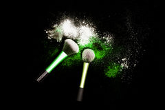 Make-up brush with colorful powder on black background. Explosion stars dust with bright colors. White and green powder. Stock Image