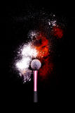 Make-up brush with colorful powder on black background. Explosion stars dust with bright colors. White and green powder red Stock Photos