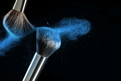 Make-up brush concept with ultraviolet, blue and orange powder explosion isolated on black background. royalty free stock photos