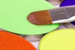 Make-up brush on green professional eyeshadows Stock Images