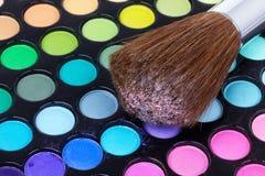 Make-up brush on multicolour eye shadows Stock Photos