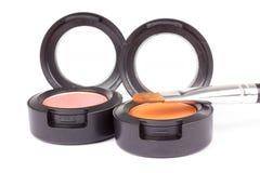 Make-up brush on orange eyeshadows in round boxes Stock Photography