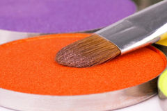 Make-up brush on orange eyeshadows round palette Royalty Free Stock Image