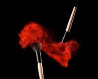 Make-up brush with powder explosion on black background stock photo