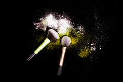 Make-up brush with white powder spilled glitter dust on black background. Makeup brush on new year`s Party with bright colors. Stock Image