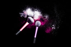 Make-up brush with white powder spilled glitter dust on black background. Makeup brush on new year`s Party with bright colors. Stock Photography