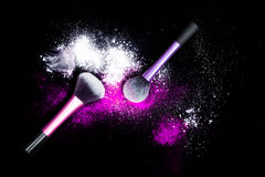 Make-up brush with white powder spilled glitter dust on black background. Makeup brush on new year`s Party with bright colors. Royalty Free Stock Photos
