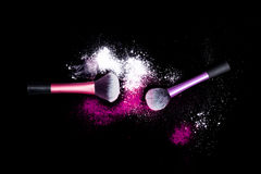 Make-up brush with white powder spilled glitter dust on black background. Makeup brush on new year`s Party with bright colors. Make-up brushes with colorful Stock Photography