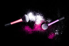 Make-up brush with white powder spilled glitter dust on black background. Makeup brush on new year`s Party with bright colors. Royalty Free Stock Image