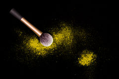 Make-up brush with yellow powder spilled glitter dust on black background. Makeup brush on new year`s Party with bright colors. Stock Image