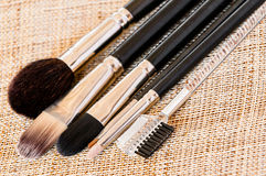 Make-up brushes. A variety of make-up brushes on a light textured surface, close-up Stock Images