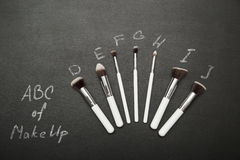 Make up brushes on black background with chulk pictures. Stock Photos