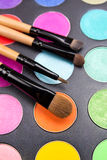 Make-up brushes and colorful eyeshadow palette over black Royalty Free Stock Image